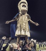 Trojan Man being lifted by the PHS cheerleaders during a night football game