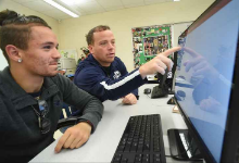 Dave Woodley point to computer screen with student looking on