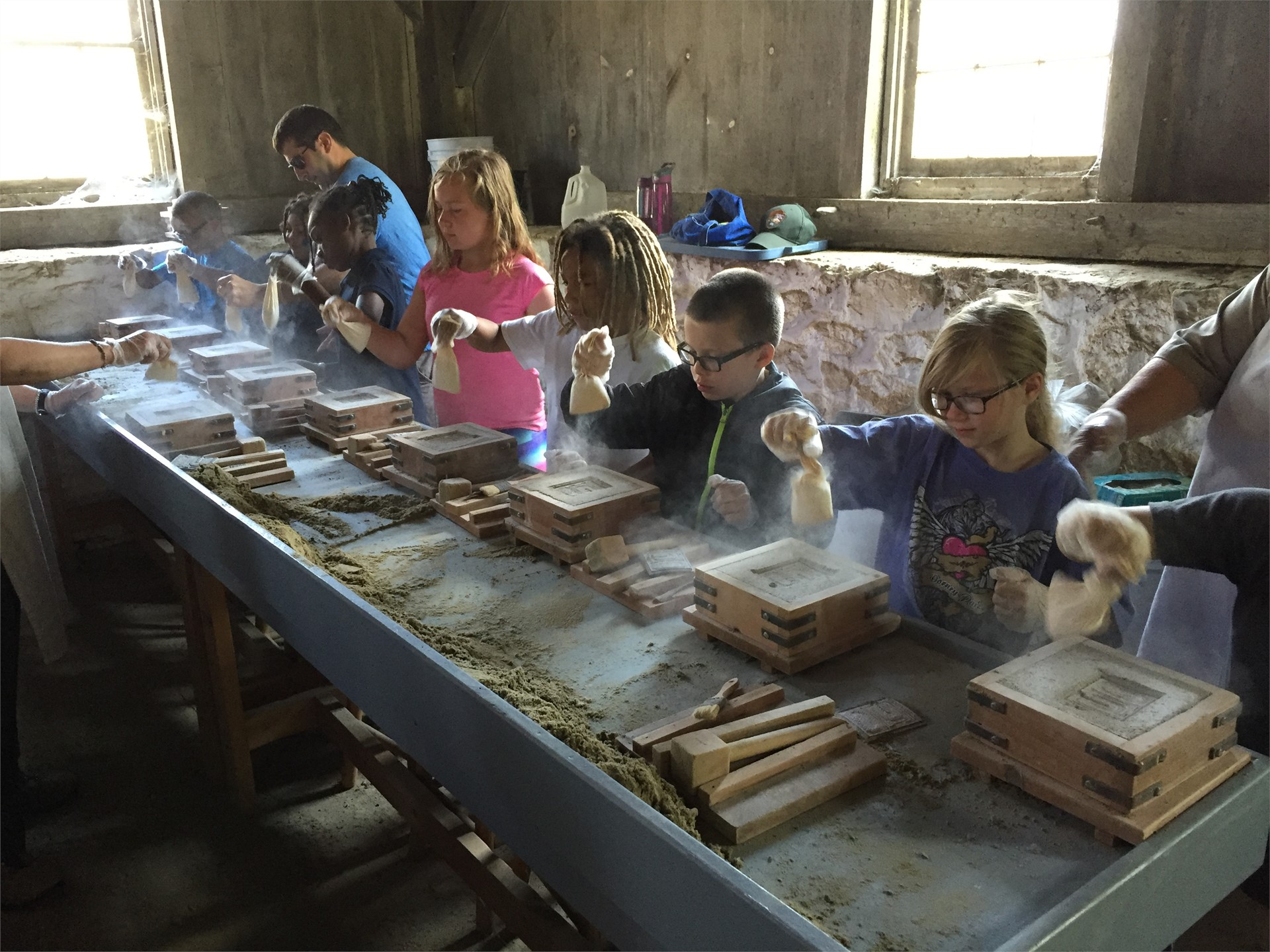 The class is hard at work making a cast of a furnace at Hopewell Furnace.