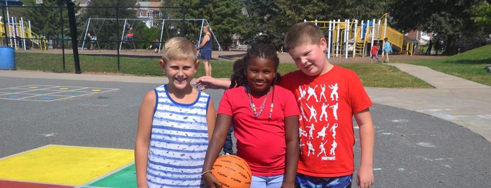 3 kids on playground with basketball