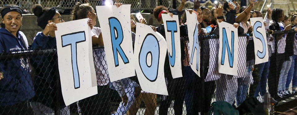 TROJANS sign being held up by students