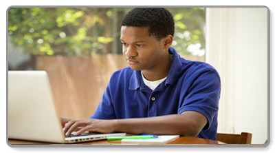 Student sitting at a laptop looking at screen.